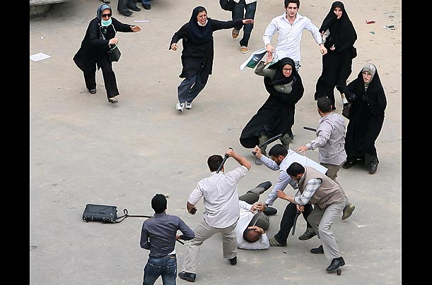 A Mousavi supporter is beaten by men with rubber batons.