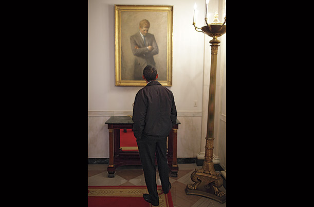 On an early tour of the White House residence, Obama stops outside the State Dining Room to consider Aaron Shikler's famous portrait of John F. Kennedy.