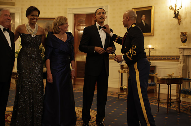 Obama allows his tie to be adjusted before the Governor's Dinner.
