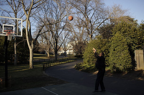 Obama pauses during his first tour of the White House grounds to try out the local rim.