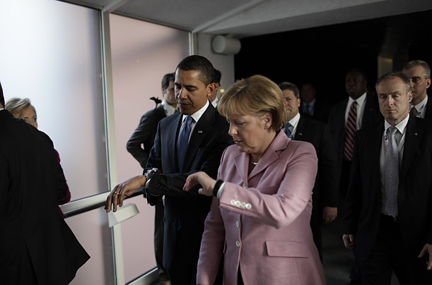 Obama and German President Angela Merkel check their watches.