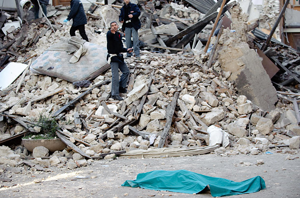 The body of a victim lies on the street in front of his collapsed house in the center of the Abruzzo capital L'Aquila