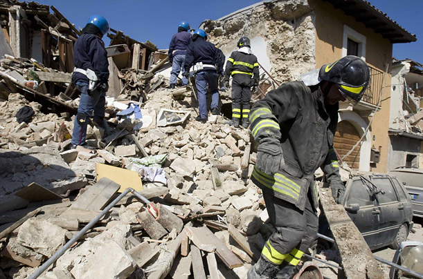 Firefighters and police sift through the wreckage of a house