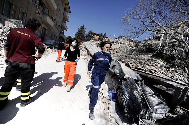 Doctors and rescue workers rush by a collapsed building in the centre of L'Aquila