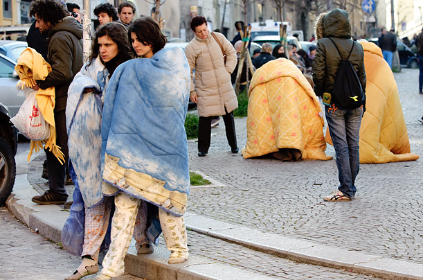 Residents of L'Auila wrap themselves in blankets to keep warm against the early morning chill having been forced out of their homes by the earthquake