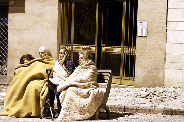Elderly women huddle on a street bench after their homes were destroyed during the night