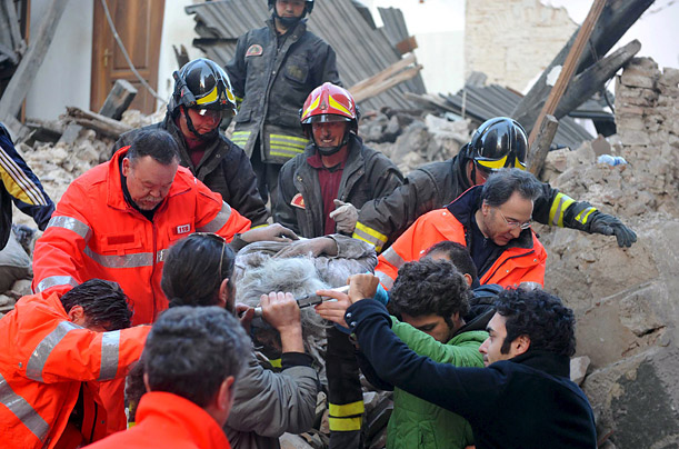 Italian rescue teams retrieve a person from a collapsed building after the earthquake struck in the early hours of the morning