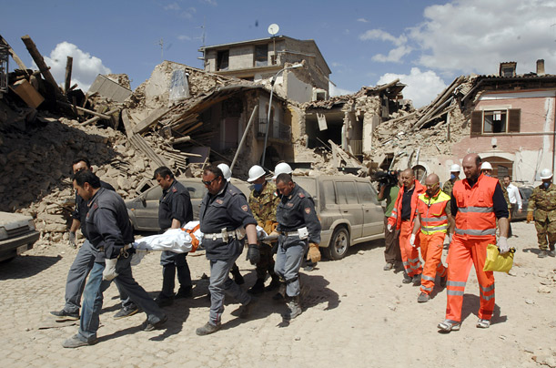 Rescuers carry a stretcher in the village of Onna