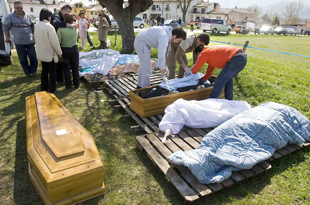 The body of an infant is placed with its mother in a coffin in the village of Onna