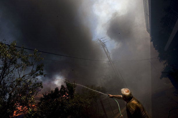 A man desperately tries to save his home from the fire in Agios Stefanos, Athens