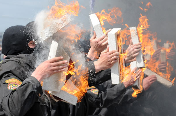 Belarusian special-forces soldiers break flaming bricks with their foreheads during a demonstration at Milex 2009, an annual armaments expo held in Minsk.
