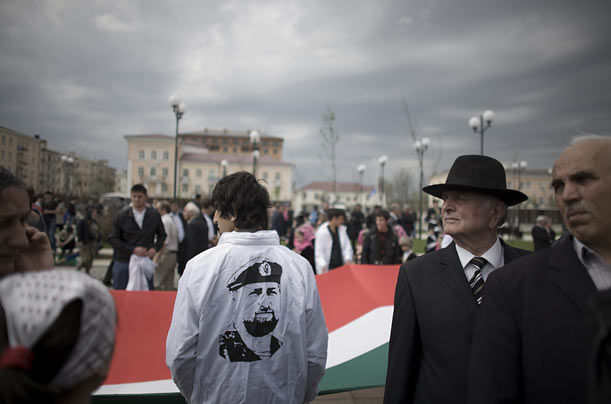 A young man wears a jacket emblazoned with Kadyrov's portrait. Though the Chechen President enjoys the support of the Kremlin,
