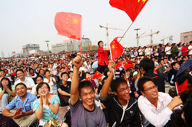 Chinese citizens gather to watch the parade at a plaza in Jinan, in the eastern Shandong province.