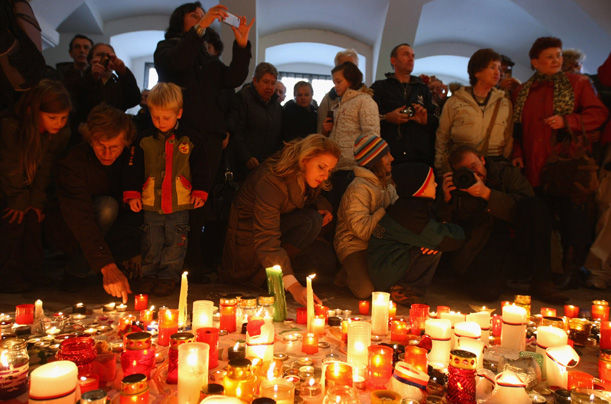 People light candles at the memorial for the Velvet Revolution in Prague's city center on November 17, 2009