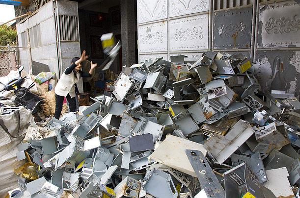 A worker throws a computer casing onto a pile.