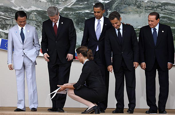 An aide removes a place marker from beneath the feet of Canadian Prime Minister Stephen Harper. Waiting beside him are: Japan's Prime Minister Taro Aso, President Obama, French President Nicolas Sarkozy and Berlusconi.