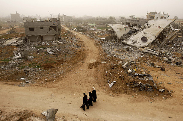 A man and two women walk through the village of Mughraqa.
