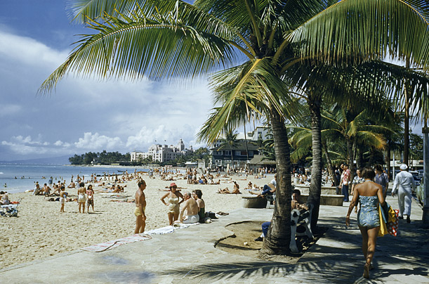 Tourists enjoy everything Honolulu has to offer on the beach-side walks in 1954