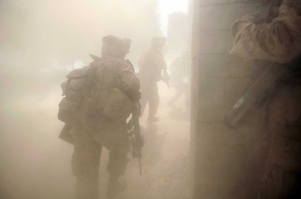 Soldiers run through a door that they blew open with explosives after taking fire from inside a compound in Mian Poshteh.