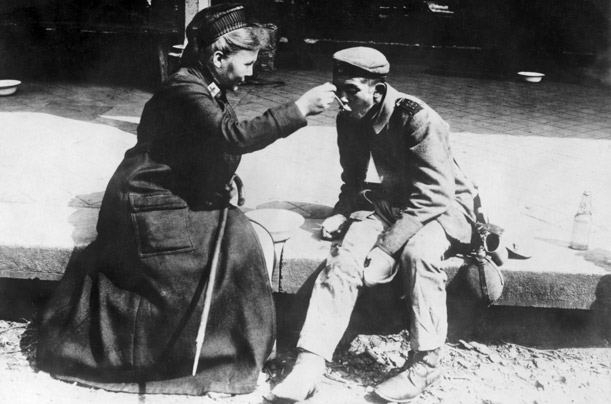 First World War, Germany.  A German Red Cross nurse helps a destitute man.