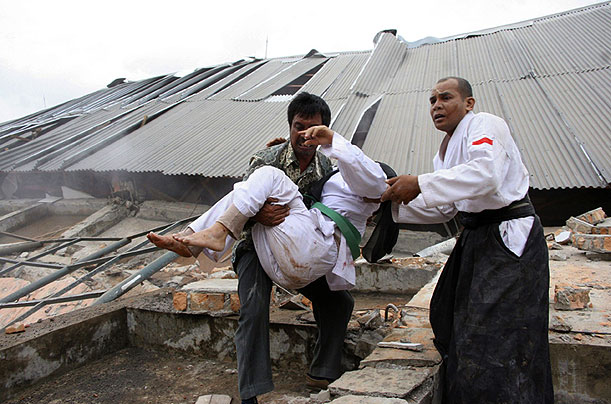 A man carries an injured person in front of a collapsed university building