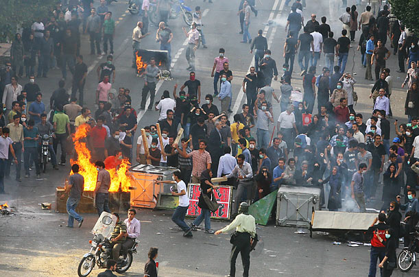 Supporters of Iran's defeated presidential candidate Mir Hossein Mousavi throw stones at riot police during a demonstration in Tehran on June 20, 2009.