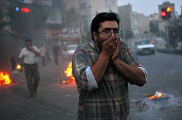An Iranian protester covers his face after a tear gas volley during clashes with riot police.