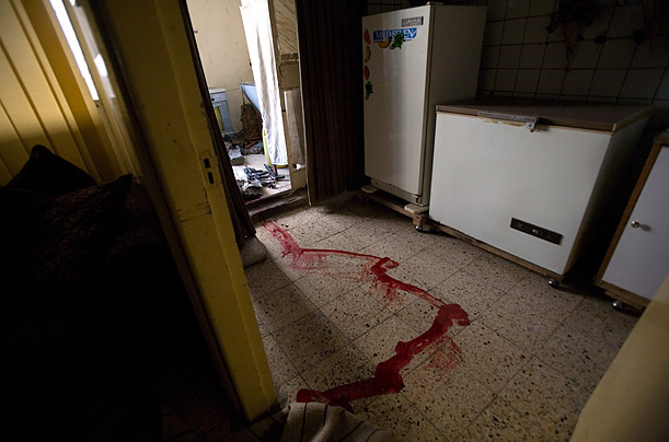 A soldier's blood lines the floor of an abandoned apartment.