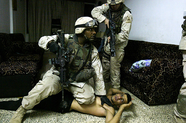 A suspected Sunni insurgent is arrested inside his home.