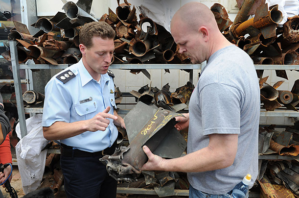 Israeli police spokesman Micky Rosenfeld shows Wurzelbacher the remains of Palestinian rocket shells.