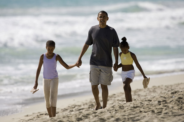 President Obama walks down Kailua Beach in Kailua, Hawaii, with his daughters