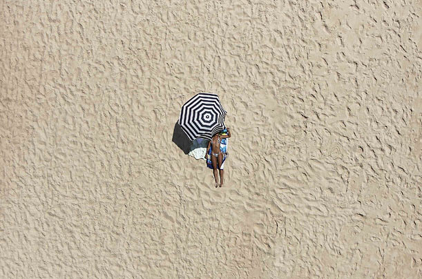 A woman works on her at a beach in Pinheiro da Cruz, Portugal.