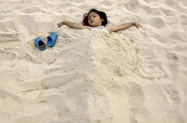 Covered  Five-year-old Liu Lin spreads her arms as she lies with her body buried in the sand at the Sun Beach Theme Park in Beijing.