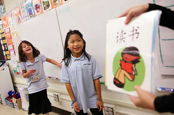 First-graders from left, Brianna Heidkamp and Alice Lind-MacMillan intrepret Chinese language cards in class. The school has tripled its enrollment since opening, with the student body now standing at 300.