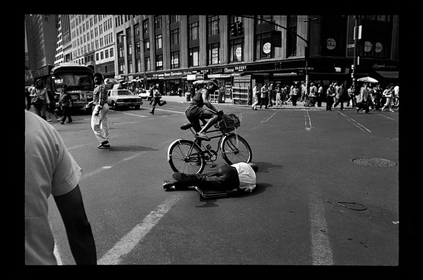 A bicyclist has to make his way round a man lying on the street