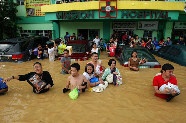 Filipinos flee a hospital in Cainta, east of Manila, as flood waters triggered by Tropical Storm Ketsana submerge its entrance