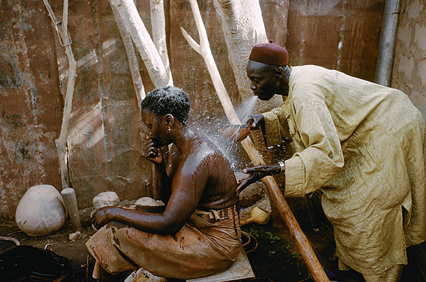 A client suffering a fertility problem is sprayed with a medicinal liquid by the son of a marabout named Ciss in Sereres. Marabouts are dervishes in Muslim Africa credited with supernatural powers.