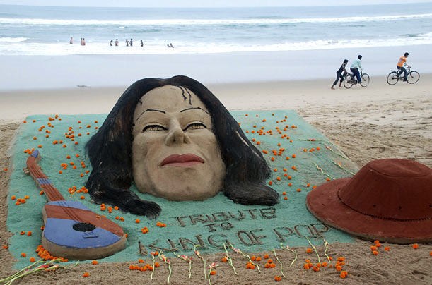 Sand sculptures of Michael Jackson, a guitar and his fedora hat, made by Sudarshan Pattnaik, stand on the beach at Puri, India.