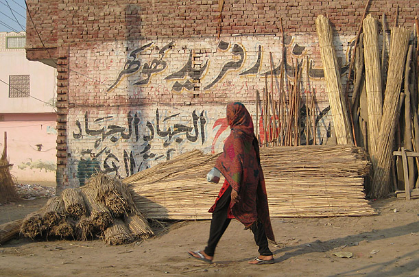 In 2005, Qasab left Faridkot, above, for Lahore. The Urdu graffiti on the wall in this photo reads,