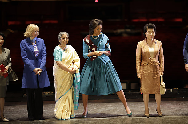 The First Lady slides into her spot alongside other G-20 spouses before a group photo at the Royal Opera House.