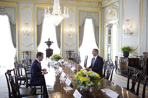 Obama and Medvedev talk meet over a meeting table.