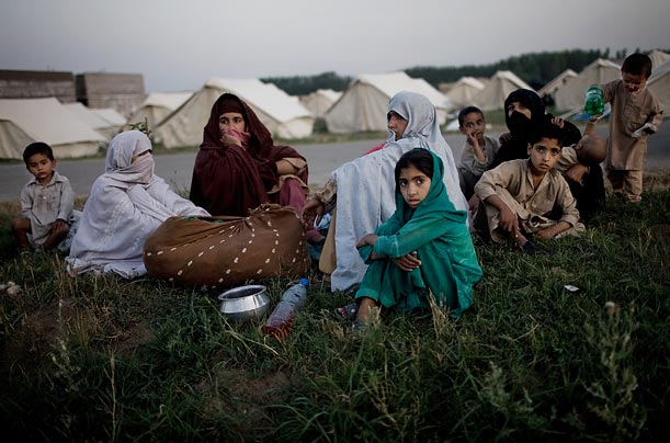 A family internally displaced by military operations in Swat waits to be given a tent at a relief camp.