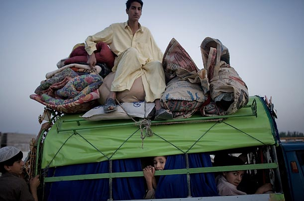 Refugees take to the road with their belongings.
