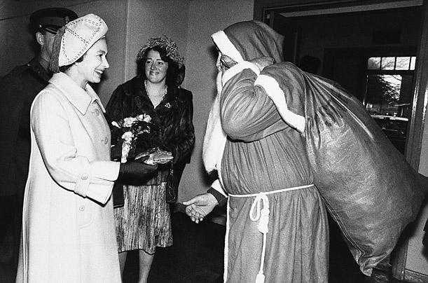 Queen Elizabeth II receives a bag of sweets for her grandson from Santa Claus, played by Colour Sergeant Ken Jones, during her 1977 visit to the 1st Battalion the Royal Welch Fusiliers at Lucknow Barracks, Tidworth