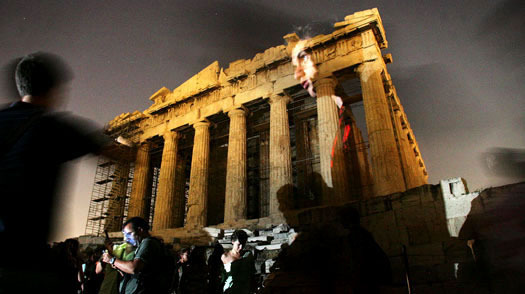 People look at the full moon rising behind the Parthenon, on the Acropolis Hill, in Athens, Greece