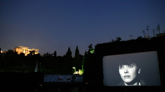 "The open-air cinema of ""Thisseion"" at Thisseion area plays the Jean-Luc Godard film ""Vivre Sa Vie"" while offers a splendid view of the archaeological site of the rock of the Acropolis"