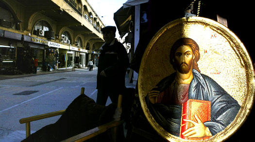 A man walks past a religious icon display in the Monastiraki flea market in Athens
