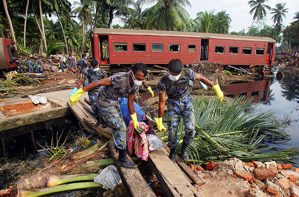Rescue workers remove bodies from the wreckage of the