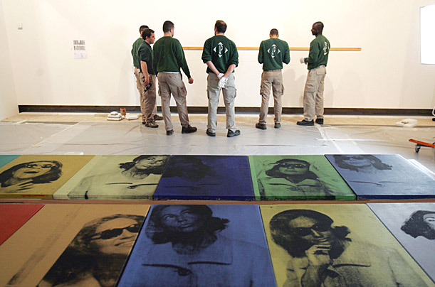 Museum employees prepare to hang up paintings by US artist Andy Warhol at the Grand Palais in Paris, Friday March 13, 2009. About 150 works of art made by Andy Warhol