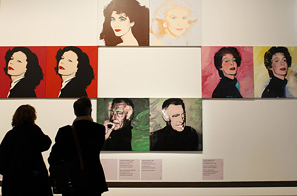 Visitors look at paintings by U.S. artist Andy Warhol during the exhibition